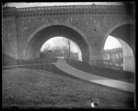 Footpath under the eastern section of the Washington Bridge, Harlem River, New York City, undated. High Bridge visible through arch.