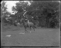 Unidentified man charging on a horse during a sham battle, Bronx, N.Y. [?], undated.