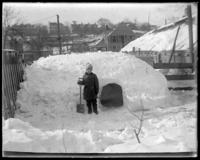 Boy in front of his snow house with a shovel, Bronx, N.Y., February 1905.