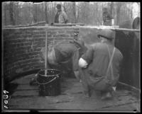 Workmen waterproofing the bear pools with paper and hot tar, New York Zoological Gardens [the Bronx Zoo], Bronx, N.Y., undated [c. 1899].