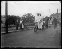 Couple on a tandem bike, bicycle parade, Bronx, N.Y., 1898.