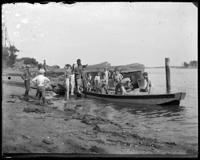 Unidentified group of boys bailing out a rowboat on the beach, Oak Point, Port Morris, Bronx, N.Y., undated [c. 1897-1905].