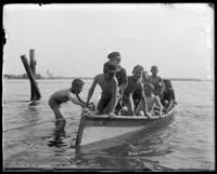 Unidentified group of boys climbing into a rowboat, Oak Point, Port Morris, Bronx, N.Y., undated [c. 1897-1905].