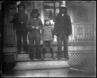 Four unidentified Native American men and boys standing on the steps of a house, Bronx, N.Y., undated [c. 1897-1910].