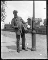 Unidentified mailman with an infant in his mailbag, Bronx, N.Y., undated [c. 1897-1917].