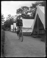 An unidentified officer of the 71st Regiment bicycling on Quality Row, State Camp (Camp Smith), Peekskill, N.Y., June 8, 1901.
