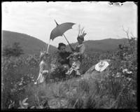 Bella, Grace, Willie, and Georgie sitting in a clearing, Garrison, N.Y., 1902. Bella putting a wreath on Georgie's head.