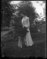 Daisy Robinson beside a tub of flowers, Garrison, N.Y., 1902.
