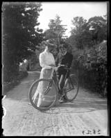 Daisy and an unidentified man posing in the road with a bicycle, Garrison, N.Y., 1903.