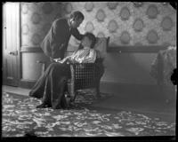 George E. Stonebridge leaning over an unidentified woman in an armchair in a romantic tableau, Bronx, N.Y. [?], undated [c. 1903].