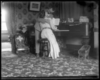 George E. Stonebridge and an unidentified woman embracing at the piano in a romantic tableau, Bronx, N.Y. [?], undated [c. 1903].