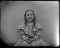 Grace Stonebridge sitting with her hands folded in her lap, Bronx, N.Y., undated [c. 1898].