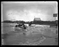 Boys trying to raise a rowboat full of water, Orchard Beach, Bronx, N.Y., 1907.