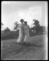 Two unidentified young women strolling past the campsites, Orchard Beach, Bronx, N.Y., 1909.