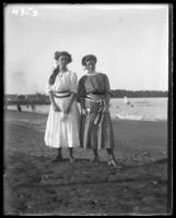Grace Stonebridge and an unidentified young woman holding small flags on the beach, Orchard Beach, Bronx, N.Y., 1907.