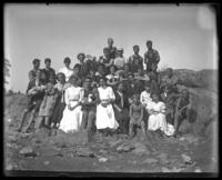 Group portrait on the rocks, Orchard Beach, Bronx, N.Y., 1907. Includes Grace Stonebridge, front, third from the left.
