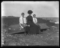 Unidentified woman and two boys seated on an overturned boat, Orchard Beach, Bronx, N.Y., September 5, 1910.