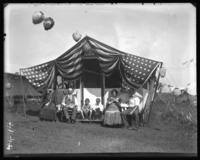Campsite decorated for Labor Day with unidentified family seated in front, Orchard Beach, Bronx, N.Y., September 5, 1910.