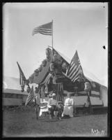 Campsite decorated for Labor Day with unidentified couple seated in front, Orchard Beach, Bronx, N.Y., September 5, 1910.