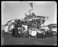 Campsite decorated for Labor Day with unidentified family posing in front with a baby carriage, Orchard Beach, Bronx, N.Y., September 5, 1910.