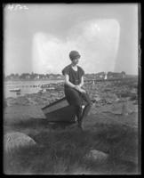 Unidentified girl in a bathing suit sitting on a beached boat, Orchard Beach, Bronx, N.Y., 1915.