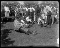 Boys putting shoes on for a race [?], Orchard Beach, Bronx, N.Y., 1909.