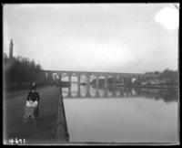 View of High Bridge, the Harlem River, and High Bridge Tower from along the Promenade, New York City, N. Y., undated [c. 1900]. Unidentified woman and infant in the foreground.