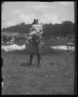 22nd Battalion man carrying wrapped packages, State Camp (Camp Smith), Peekskill, N.Y., June 13, 1903.