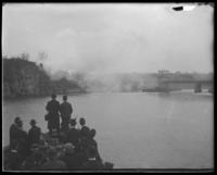Boat with visiting members of Congress going through the Harlem Ship Canal, New York City, May 5-6, 1903. The Second Battery firing a salute from a nearby bluff.