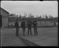 Four unidentified military officers on a dock during an excursion with the  North Side Board of Trade and the Congressional Rivers & Harbors Committee, New York City, May 5 or 6, 1903.