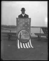 Rep. Stephen M. Sparkman of Florida holding coat of arms for his state on the deck of the 'Fulton Market' during the Congressional Rivers & Harbors Committee visit to New York City with the North Side Board of Trade, May 5 or 6, 1903.
