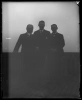 Three unidentified officials from the North Side Board of Trade and the Congressional Committee on Rivers and Harbors on the deck of a boat, Yonkers, N.Y. [?], 1906.
