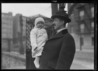 Unidentified baby in coat and woolly hat, held by a man in a fedora, New York City, undated (ca. 1916-1917).