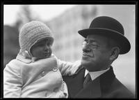 Unidentified baby in coat and woolly hat, held by a man in a bowler hat, New York City, undated (ca. 1916-1917).