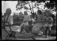 William Gray Hassler and four unidentified girls, seated on park benches, talking, Isham Park, Inwood, New York City, undated (ca. 1913-1914).