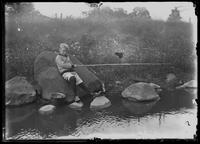 William Gray Hassler at the edge of a stream, holding a fishing pole, undated (ca. 1913-1914).