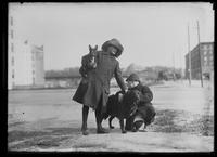 Unidentified boy and girl posing on a city street with two dogs, undated (ca. 1913-1914).