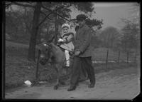 Unientified little girl being given a ride on a donkey, Central Park (?), New York City, undated (ca. 1913-1914).