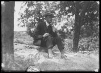 Unidentified young man in a straw boater sitting on a rock in a park, undated (ca. 1913-1914).