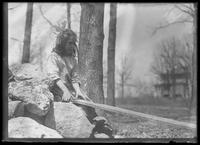 Mary Hassler playing with a plank near a pile of rocks, undated (ca. 1913-1914).