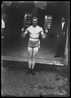 English boxer William Thomas Wells (Bombardier Billy Wells), posing with meels, undated (ca. 1910).