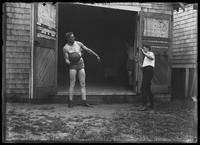 English boxer William Thomas Wells (Bombardier Billy Wells) and sparring partner 'Syd' cavort with a medicine ball, undated (ca. 1910).