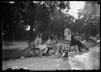 William Gray Hassler with four unidentified little girls in a park, talking and laughing, Isham Park, Inwood, New York City, undated (ca. 1913-1914).