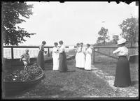 William Gray Hassler, Ethel Magaw Hassler, and several unidentified women in the back garden of an unidentified house on a lake or river, examining cameras, undated (ca. 1911-1914).