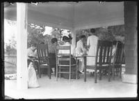 Ethel Magaw Hassler and several unidentified women seated around a dining table on a verandah, undated (ca. 1911-1915).