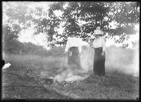 Belle Hassler Welty (?) and unidentified woman tending a small fire under a tree, undated (ca. 1911-1915).