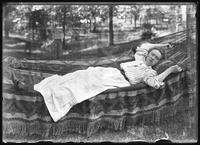Ethel Magaw Hassler in a hammock, undated (ca. 1905-1910). Double exposure with an item of printed material.