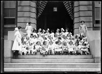 Group portrait of children from the Roman Catholic Orphan Asylum, Kingsbridge, Bronx, seated on steps, undated (ca. 1912).