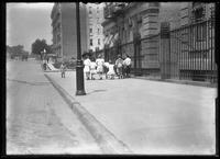 William Gray Hassler and a group of unidentified children walking down the sidewalk, New York City, undated (ca. 1912).