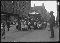 Children gathered around a street carousel, probably the Lower East Side, New York City, undated (ca. 1915).